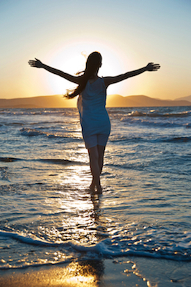 Woman Walking on the Beach Enjoying the Benefits of Energy Balancing Therapy